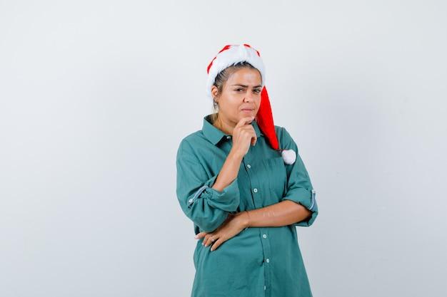 Giovane donna con cappello di natale, camicia con il dito sul mento e sguardo pensieroso, vista frontale.