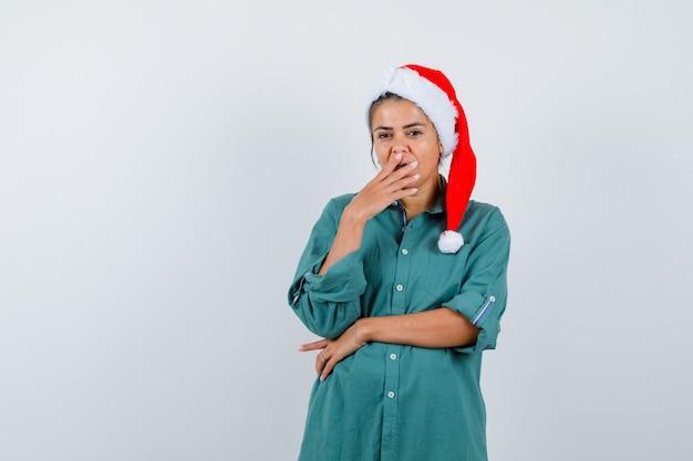 Giovane donna con cappello di natale, camicia con la mano sulla bocca e sguardo perplesso, vista frontale.