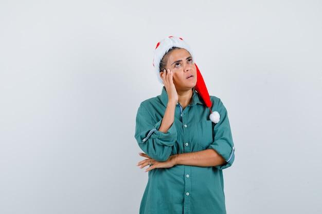 Giovane donna con cappello di natale, camicia con la mano vicino al viso e sguardo pensieroso, vista frontale.