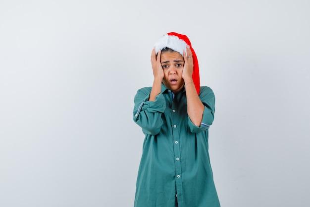 Giovane donna con cappello di natale, camicia con le mani sulla testa e sguardo spaventato, vista frontale.