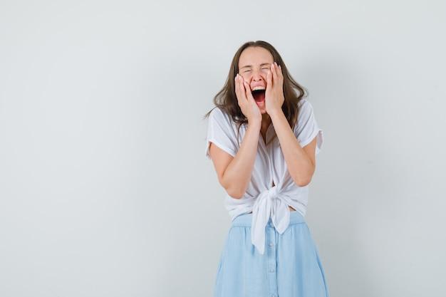 Молодая дама в белой блузке, синей юбке и радостном взгляде обнимает лицо руками.