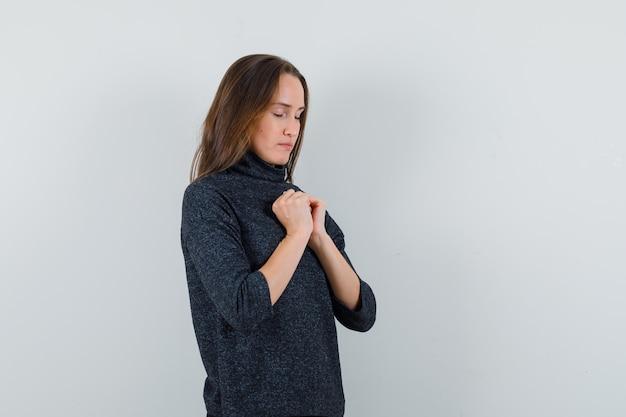 Giovane donna che stringe le mani nel gesto di preghiera in camicia casual e sembra calma