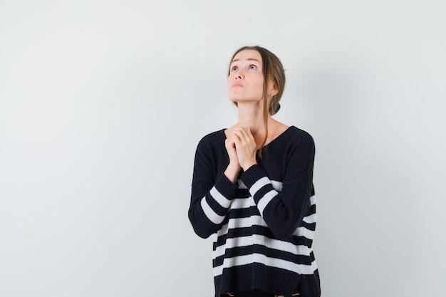 Giovane donna che stringe le mani nel gesto di preghiera in camicia casual e sembra speranzoso