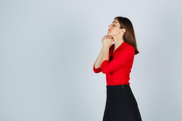 Giovane donna che stringe le mani in posizione di preghiera in camicetta rossa