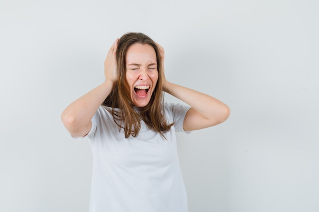 Young lady clasping head while screaming in white t-shirt and looking excited
