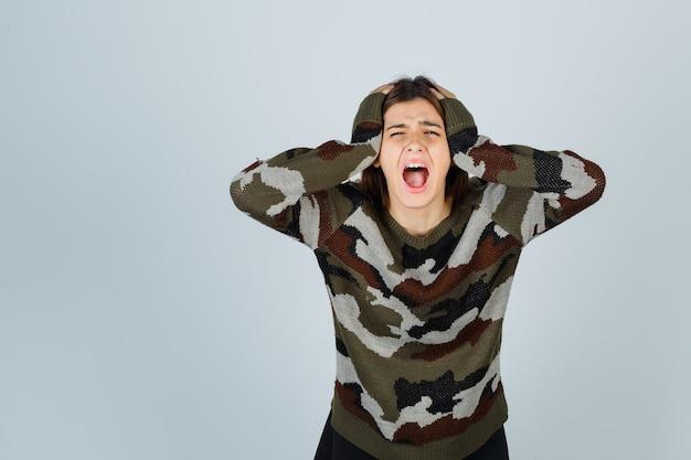 Giovane donna che stringe la testa con le mani, piange in maglione e sembra addolorata