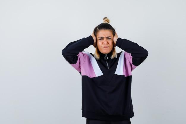 Giovane donna che stringe la testa con le mani in un maglione con cappuccio e sembra infastidita