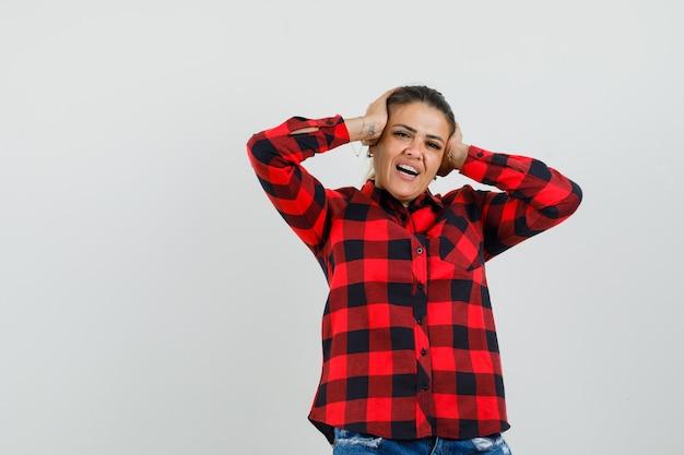 チェックシャツ、ショートパンツ、陽気に見える手で頭を握り締める若い女性。