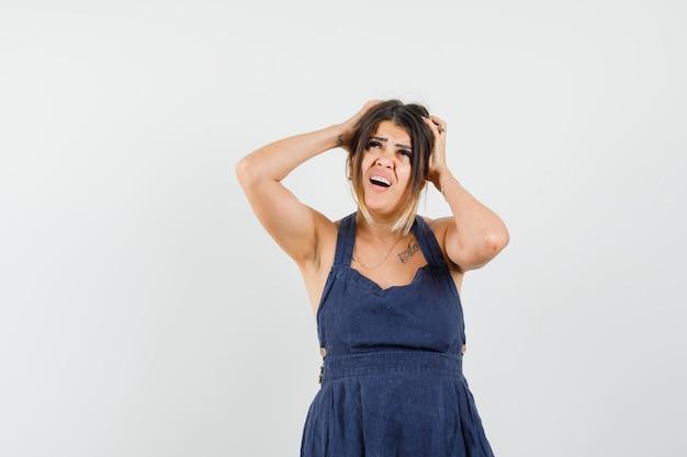 ドレスを着た手で頭を握りしめ、混乱しているように見える若い女性