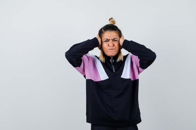 パーカーのセーターで手で頭を握りしめ、イライラしている若い女性