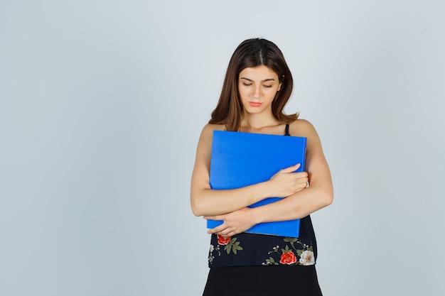Giovane donna che stringe la cartella sul petto in camicetta, gonna e sembra sconvolta, vista frontale.