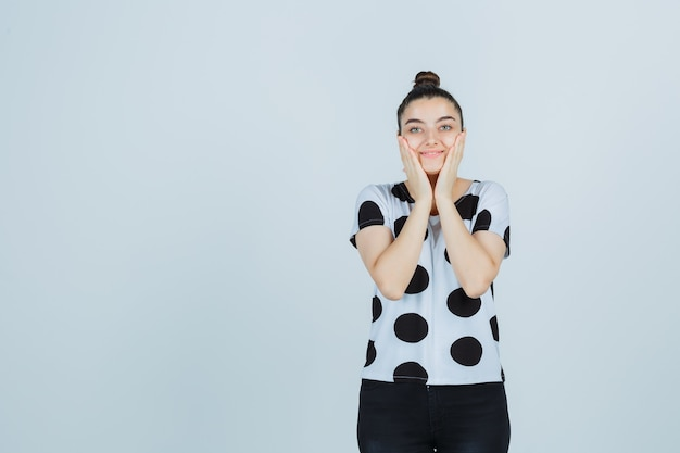 Девушка закрыла щеки руками в футболке, джинсах и выглядела мило, вид спереди.