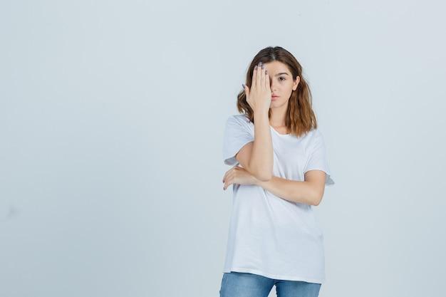 Giovane donna che copre gli occhi con la mano in t-shirt, jeans e sembra seria. vista frontale.