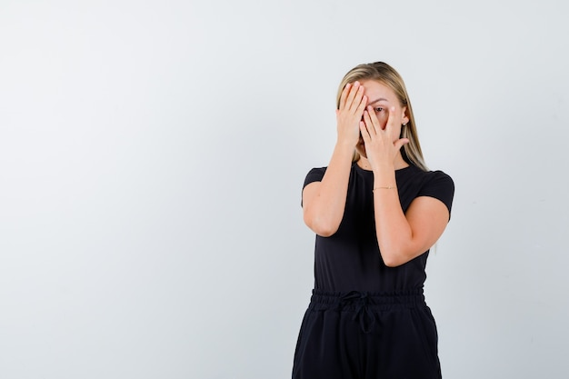 Young lady covering eye with hand while looking through fingers in t-shirt, pants and looking scared. front view.