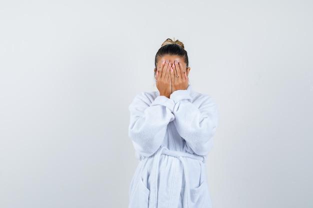 バスローブを着て手で顔を覆い、自信を持って見える若い女性
