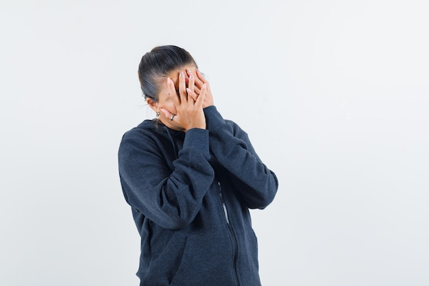 Young lady covering face with hands in jacket and looking upset. front view.