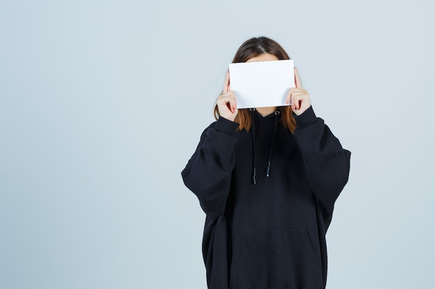 Young lady covering face with paper in oversized hoodie, pants and looking cute , front view.