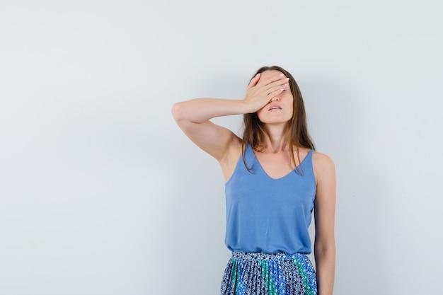파란색 블라우스, 치마에 손으로 그녀의 눈을 가리고 피곤한 젊은 아가씨. 전면보기.