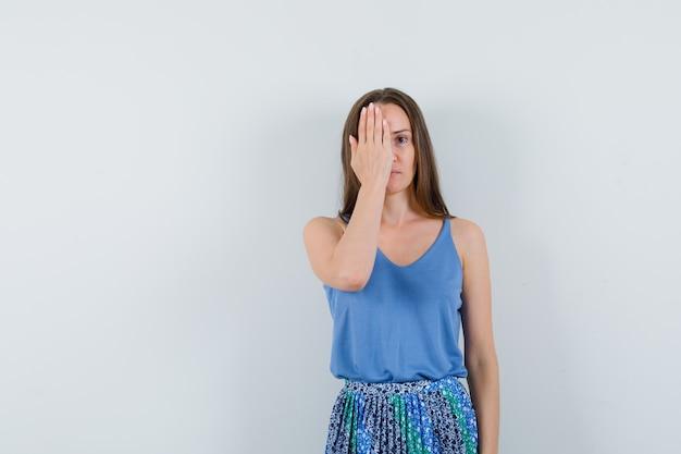 파란색 블라우스, 치마에 손으로 그녀의 절반 얼굴을 덮고 집중 찾고 젊은 아가씨. 전면보기. 텍스트를위한 공간