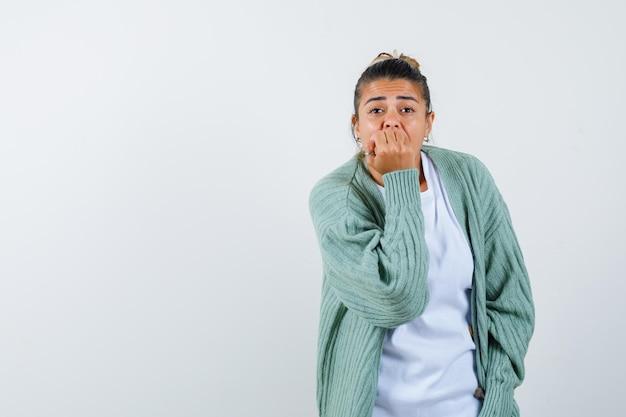 Tシャツ、ジャケットで拳で口を覆い、思慮深く見える若い女性