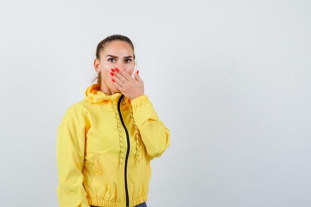 Giovane signora che copre la bocca con la mano in giacca gialla e sembra scioccata. vista frontale.