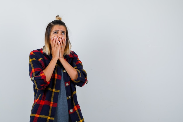 Giovane donna che copre la bocca con le mani in camicia casual a quadri e sembra sconvolta, vista frontale.