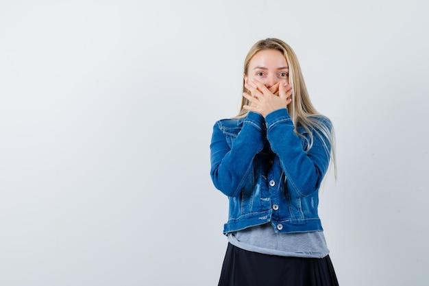 T- 셔츠, 데님 재킷, 치마에 손으로 입을 덮고 자신감을 찾고 젊은 아가씨.