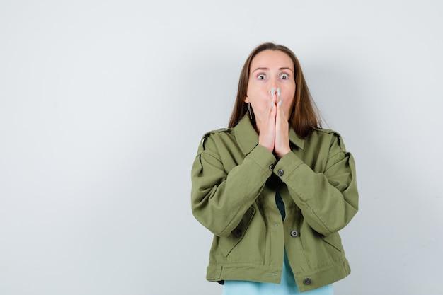 Tシャツ、ジャケット、怖い顔、正面図で手で口を覆っている若い女性。