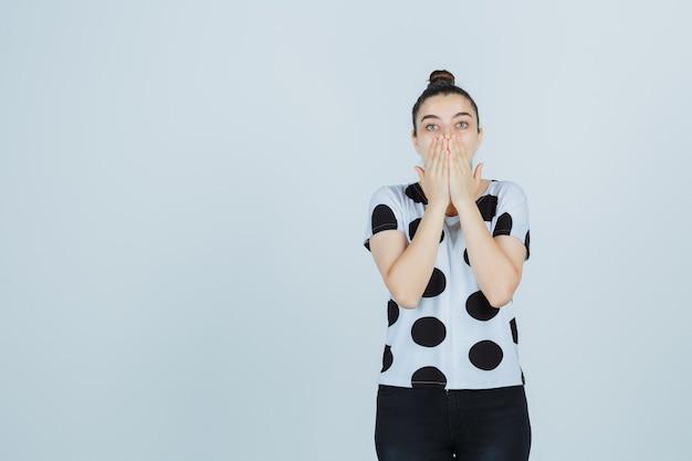 Giovane signora che copre la bocca con le mani in maglietta, jeans e che sembra felice. vista frontale.