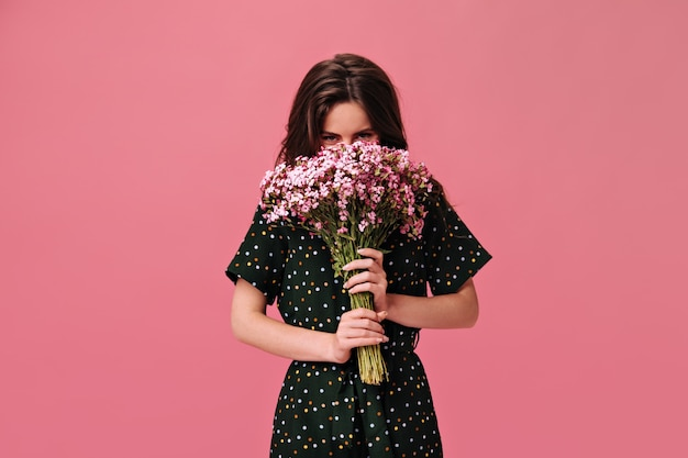 若い女性は孤立したピンクの花束で彼女の顔を覆います