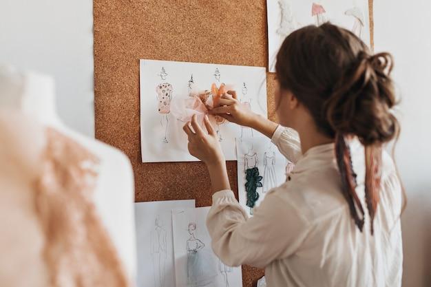 La giovane donna crea campioni di abiti