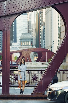 Young lady crossing the bridge in the city