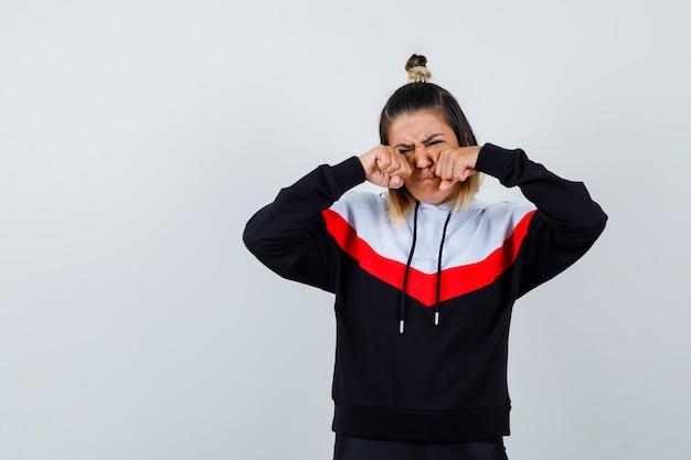 パーカーのセーターで拳で目をこすりながら泣き悲しそうな若い女性。