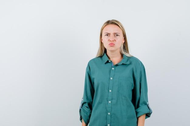 Giovane donna che curva le labbra in camicia verde e sembra cupa