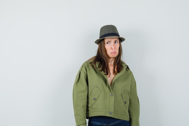 Young lady curving lips in jacket pants hat and looking sorrowful