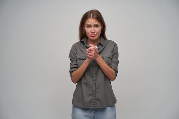 若い女性、茶色の長い髪のかわいい女性。灰色のシャツとジーンズを着ています。彼女の手を一緒に保ち、あなたに懇願します。灰色の背景の上に隔離されたカメラで動揺を見て