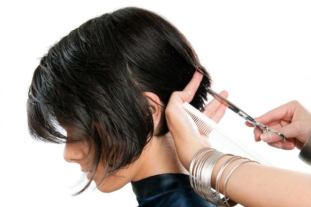 若い女性は白で隔離される美容院で髪をカット