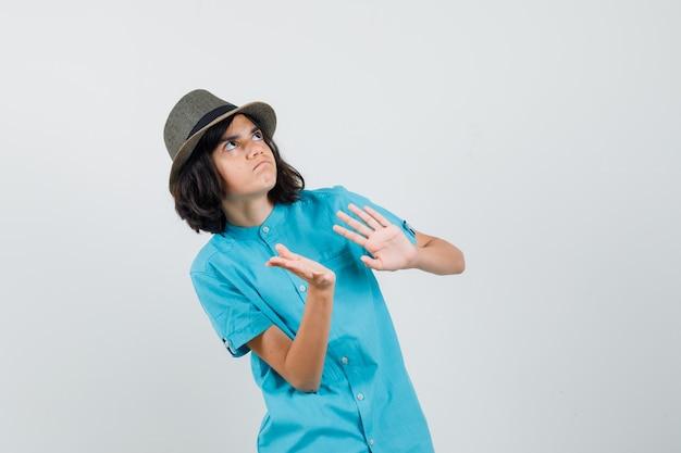 青いシャツ、帽子をかぶった手で防御し、警戒している若い女性。