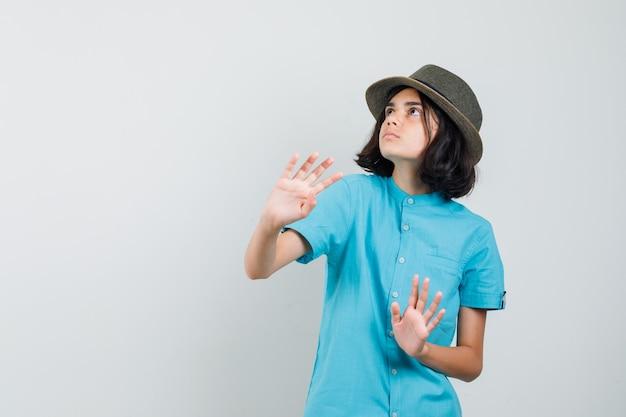 青いシャツ、帽子の手で守る若い女性
