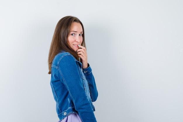 Giovane donna in giacca di jeans che tocca il labbro con un dito e si vergogna.