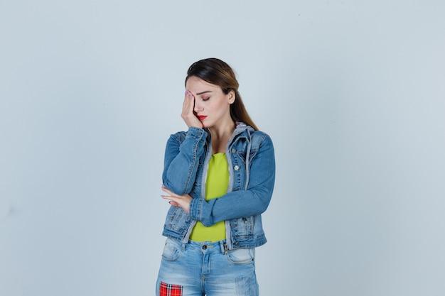 Giovane donna in abito di jeans che soffre di emicrania e sembra affaticata, vista frontale.