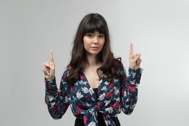 Young lady in designed t-shirt pointing out her fingers with long hair on white