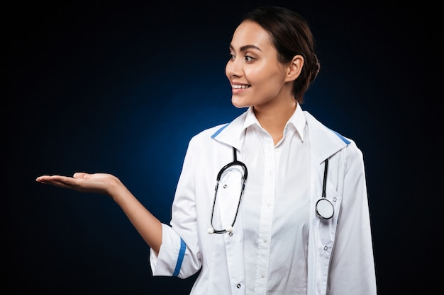Young lady doctor holding copy space on hand