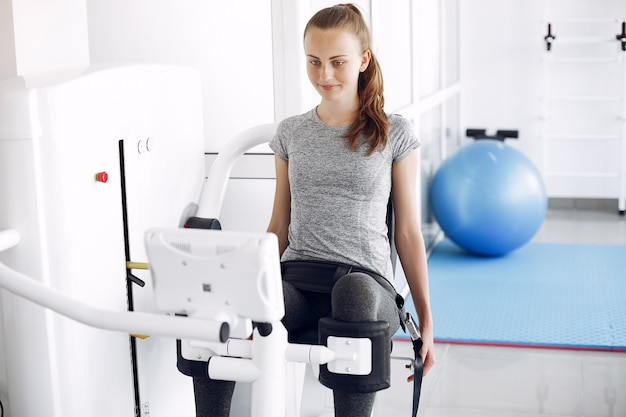 Девушка делает упражнения на тренажере в кабинете физиотерапии