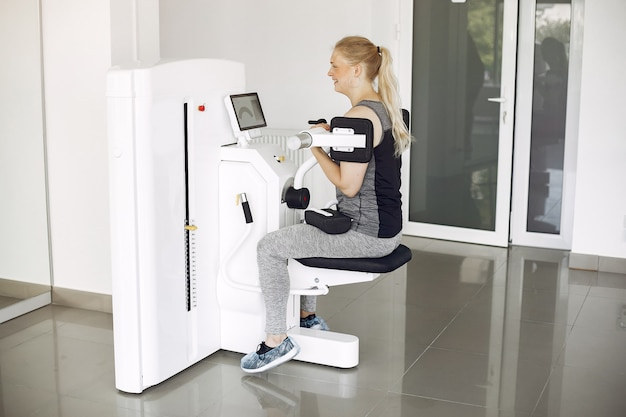 Young lady doing exercises on simulator in phisiotherapy room