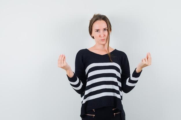 Молодая леди делает итальянский жест в повседневной рубашке и выглядит разумно