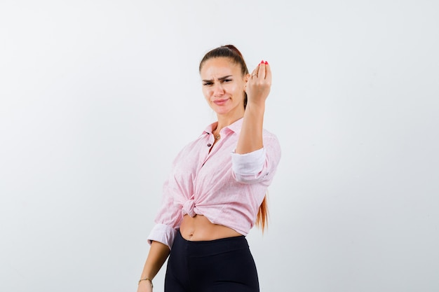 Young lady doing italian gesture in shirt, pants and looking displeased