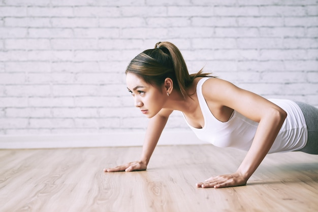 Young lady doing push-ups on the floor at home with loft design