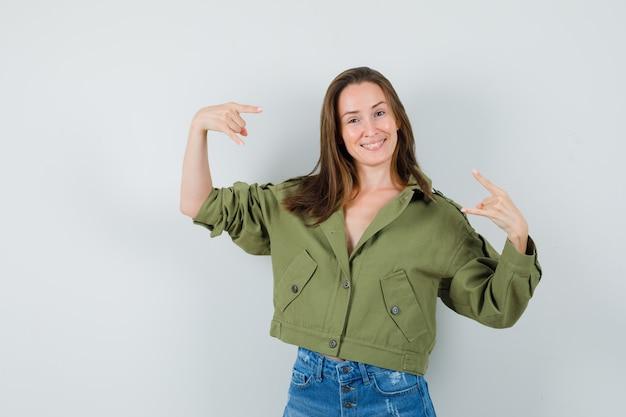 緑のジャケットのショートパンツでロックシンボルをやって、自信を持って見える若い女性