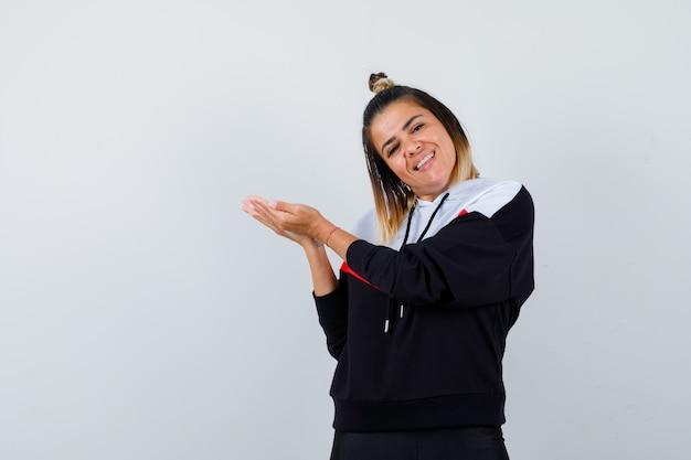 Giovane donna che fa un gesto di benvenuto con un maglione con cappuccio e sembra felice